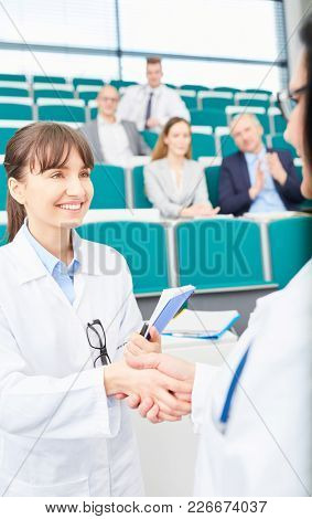Medicine teacher congratulate student for passed exam in medical school