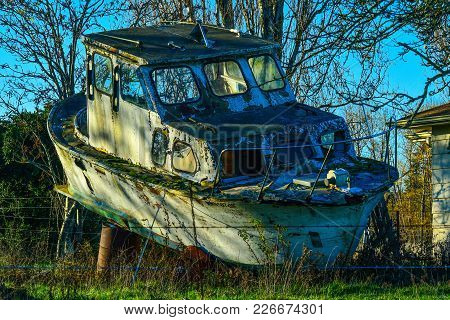 Old Boat Sitting On Blocks In Farm Yard, Covered In Moss And Sitting On Barrels
