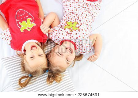 Two Children Lie In A Pajamas Bed. The Concept Of Childhood, Lifestyle, Morning. Copy Space. The Con