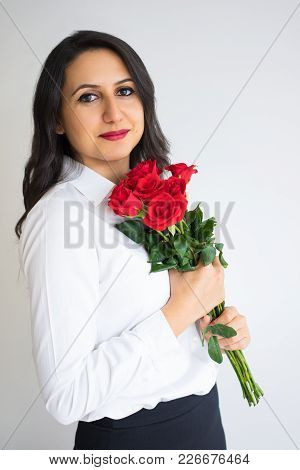 Smiling Confident Young Woman In Formalwear With Flowers Looking At Camera. Calm Beautiful Business