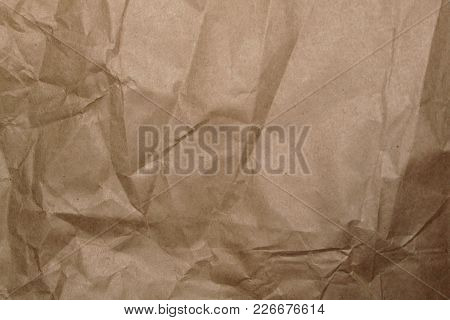 Crumpled Paper Texture, A Sheet Of Rough Craft Paper With Creases And Shadows.