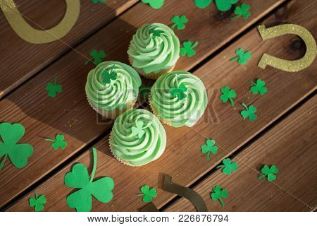 st patricks day, holidays and celebration concept - green cupcakes, horseshoes and shamrock on wooden table