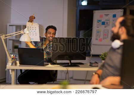 business, deadline and web design people concept - happy creative man showing papers to colleague at night office