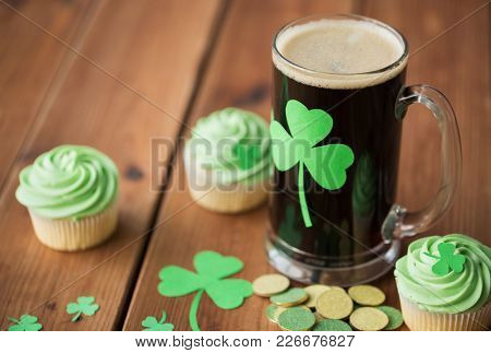 st patricks day, holidays and celebration concept - glass of dark draft beer with shamrock, green cupcakes and gold coins on wooden table
