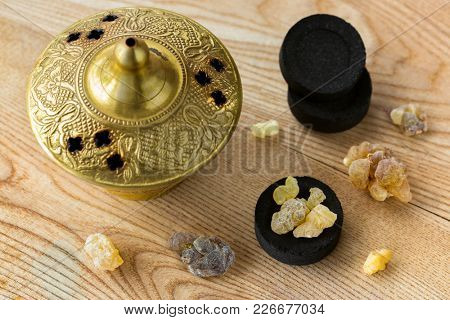 Aromatic yellow resin gum from Sudanese Frankincense tree on Arabian charcoals to burn aromatic incense in brass burner.