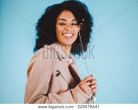 Sparkling Bengal Fire In African American Woman's Hand On Blue Background. Christmas Holiday Concept