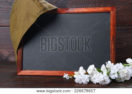 Chalkboard With Empty Space, Military Cap And Red Star On A Wooden Table. Day Of The Defender Of The