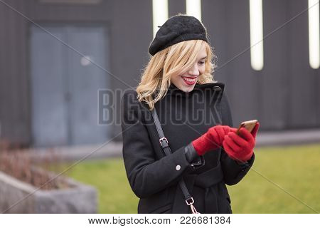 Beautiful Stylish Young Woman Typing A Text Message On Her Touchscreen Phone