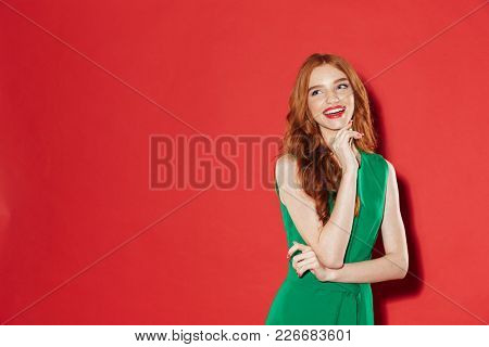 Smiling ginger woman in green dress posing with arm near chin and looking away over red background