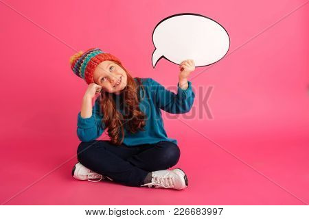 Cheerful ginger girl in hat holding bubble speech and looking up while sitting on floor