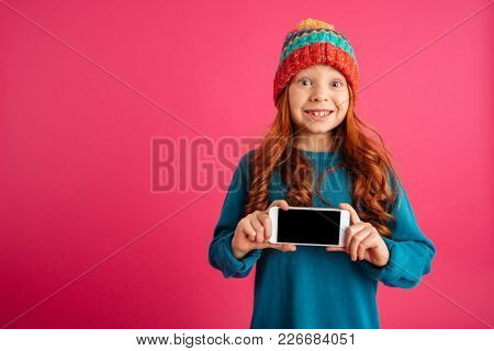 Surprised happy redhead girl showing smartphone with blank screen and smiling isolated over pink