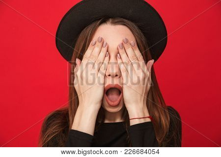 Picture of excited young woman standing isolated over red background covering eyes with hands.
