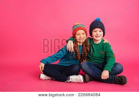 Cheerful brother and sister in knitted clothes hugging and looking camera isolated over pink background