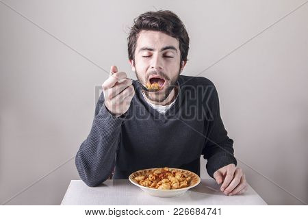 Young Caucasian Man, Starving For Food, Ravenously Going For A Plate Of Pasta