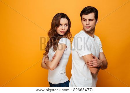 Displeased young couple standing with one another's back while looking to each other with crossed arms over yellow background