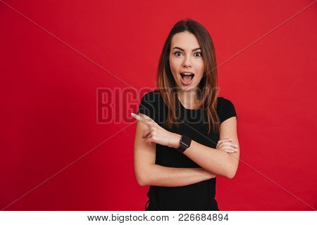 Excited optimistic woman with open mouth in black t-shirt looking at camera and pointing index finger aside on copyspace isolated over red background