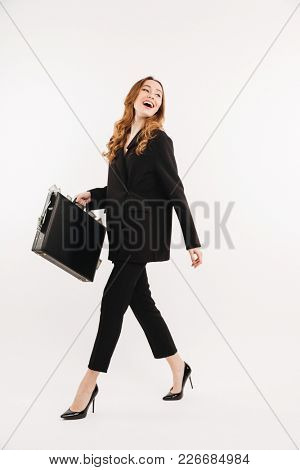 Full length portrait of a cheerful young businesswoman dressed in suit holding briefcase full of cash while walking isolated over white background