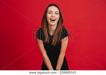 Portrait of fascinating brunette woman looking at camera and smiling with perfect white teeth isolated over red background