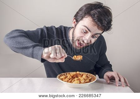 Young caucasian man, starving for food, ravenously going for a plate of pasta poster