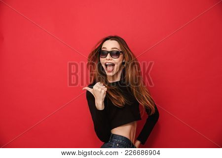 Photo of excited young woman standing isolated over red background. Looking aside pointing.