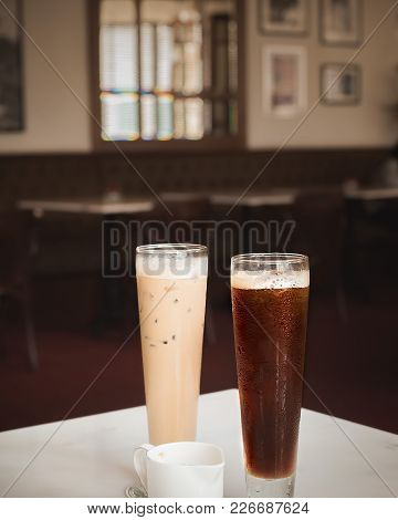 Black Coffee Luwak In Tall Glass With Caffè Latte In Empty Cafe Or Restaurant