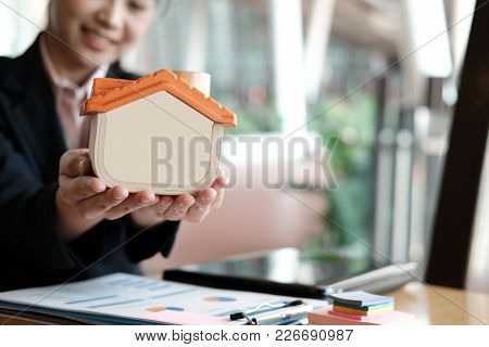 Young Realtor Holding House Model At Office. Real Estate Agent Showing Property For Sale At Workplac