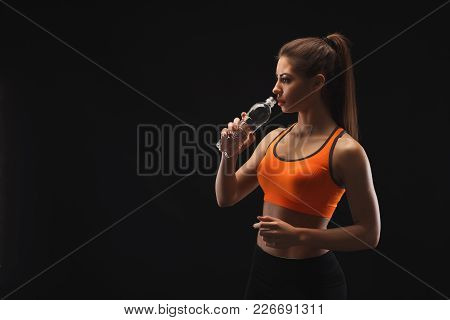 Athletic Young Woman Having Rest After Bobybuilding Training, Drinking Water On A Black Background.