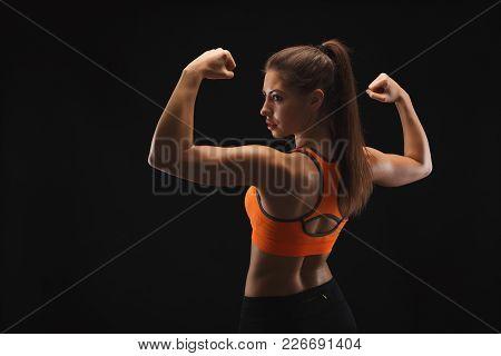 Athletic Female Fitness Model Showing Muscular Body. Studio Shot On Black Background, Low Key. Bodyb
