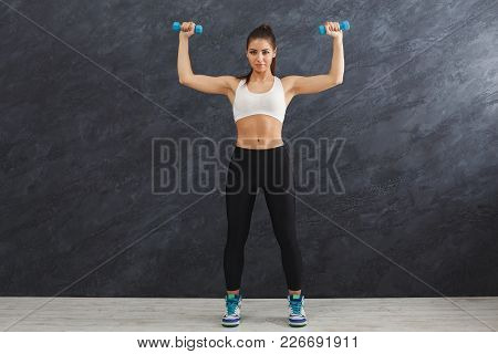 Fitness Model Woman With Dumbbells On Grey Studio Background. Young Girl In Fitwear With Sport Equip