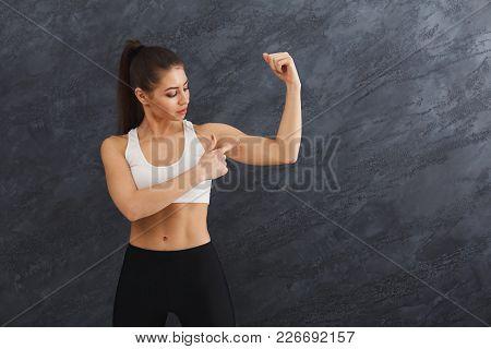 Athletic Female Fitness Model Showing Muscular Body. Studio Shot On Grey Background, Low Key. Bodybu