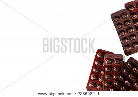 Pile Of Tablets Pills Medicine In Light Resistant Blister Pack On White Background . Vitamins And Mi
