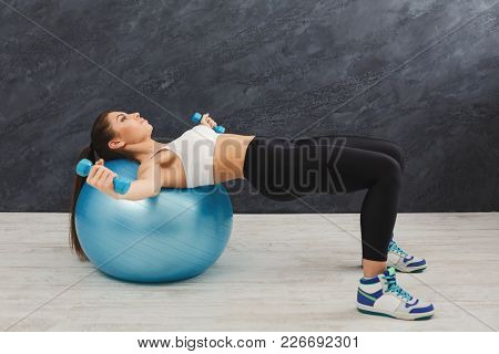 Fitness Woman Training With Fitness Ball And Dumbbells At Gym. Young Slim Girl Making Aerobics Exerc