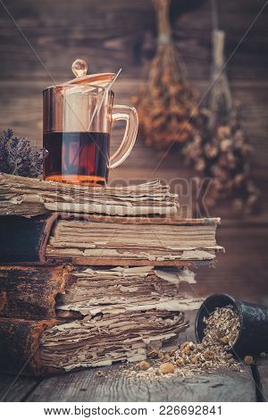 Cup Of Healthy Tea Or Herbal Tincture On Stack Of Old Books, Mortar Of Daisy Herbs. Hanging Bunches