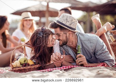 Happy Couple Lying On A Blanket And Kissing On The Beach.