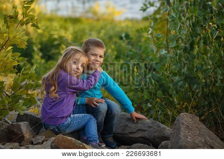 Family Time. Brother And Sister Are Sitting On Rocks And Embracing. Walk In The Forest.