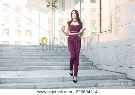 Confident Successful Businesswoman Taking City Walk At Lunch Time, Holding Take Away Coffee And Tabl