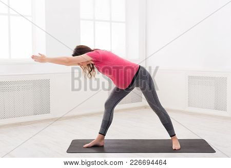 Pregnant Woman Stretching Back Training At Home, Copy Space. Expectant Female Makes Warmup Aerobics