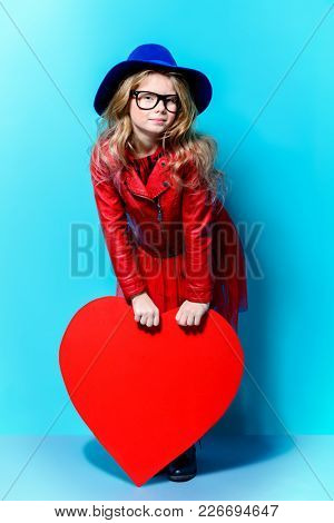 Full length portrait of a pretty pre-teen girl holding big red heart over blue background. First love. Valentine's Day.