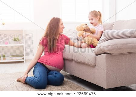 Pregnant Mother With Her Cute Little Daughter Playing With Teddy Bear, Having Fun Together, Copy Spa