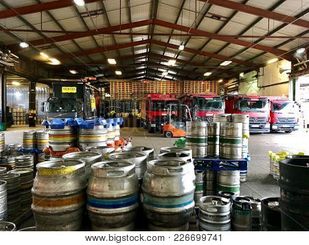 LONDON - FEBRUARY 12, 2018: Beer barrels waiting to be loaded onto commercial delivery vehicles at a loading area at The Fuller's Griffin Brewery in Chiswick, West London, UK.