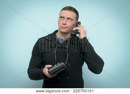 The Bored Person Man Reluctantly Talks On Phone Handset And Looks Up. Unpleasant, Boring Conversatio