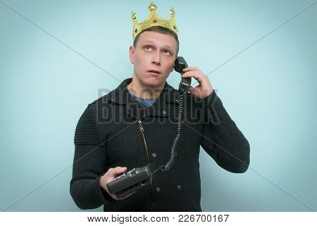 Arrogant And Smug Hot Line Consultant Or Manager With Golden Crown Above His Head Is Talking On Hand