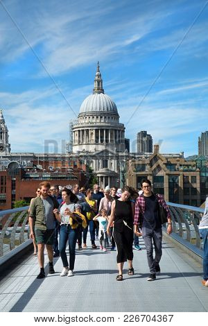 LONDON, UK - June 10th , 2017:  Tourists walking across the Millennium bridge to St. Paul Cathedral by a cloudy day in London