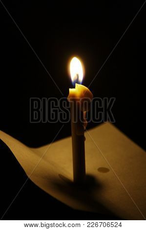Burning Wax Candle With A Wick On A Dark Background