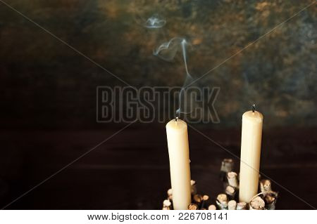 Two Faded Candles Stand On A Dark Background. Smoke From The Wick. Place And Background For Your Tex