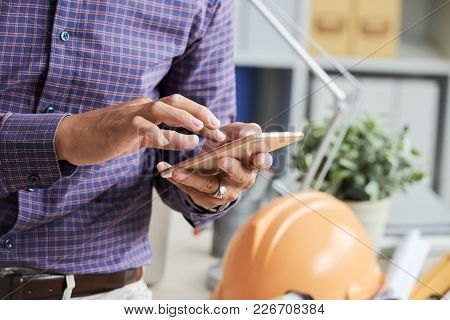 Close-up Image Of Engineer Checking Messages On His Smartphone