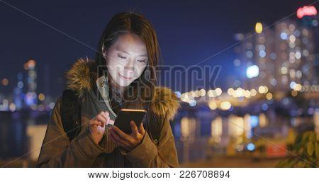 Asian Woman using cellphone in Hong Kong at night
