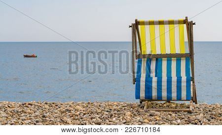 Empty Deck Chair On The Pebble Beach In Beer, Devon, Uk - With A Fishing Boat In Seaton Bay At The B