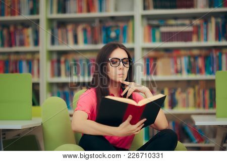 Studious Girl Reading A Book In A Library