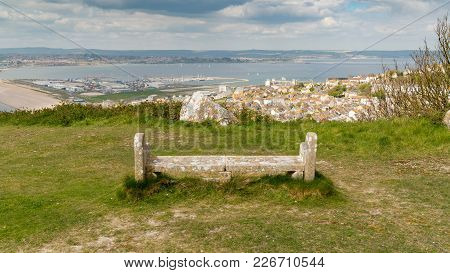 A Stone Bench On The South West Coast Path  With View Towards Fortuneswell And Chesil Beach, Isle Of
